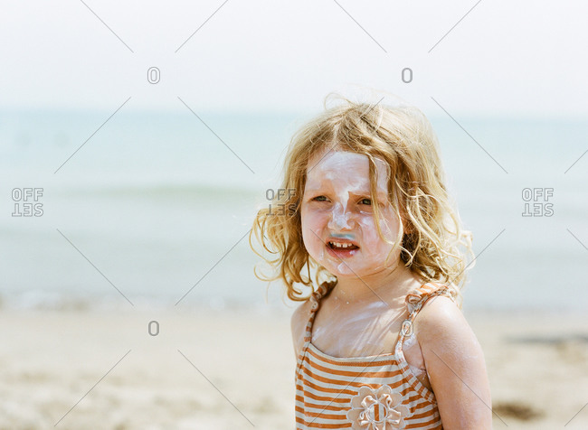Girl with sunscreen on her face looks upset