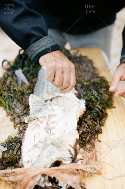 Man scaling baked fish on table