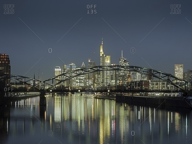 View to Osthafenbruecke and skyline with financial district at night