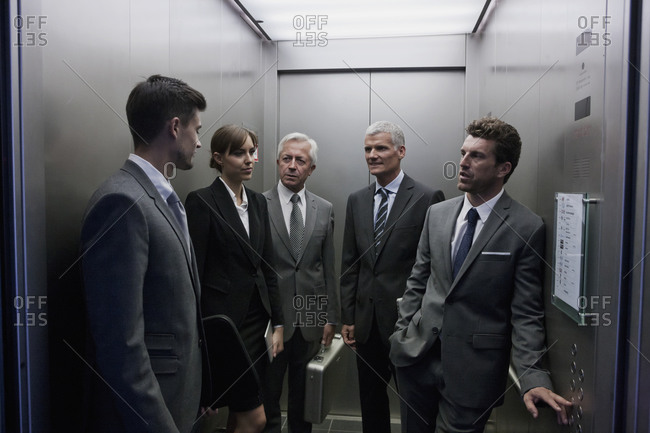 Group of businesspeople discussing in elevator
