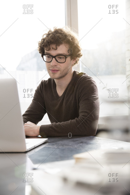 Portrait of young professional using laptop in his office