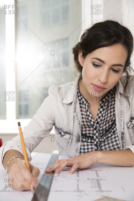 Portrait of young female architect working at her desktop in office