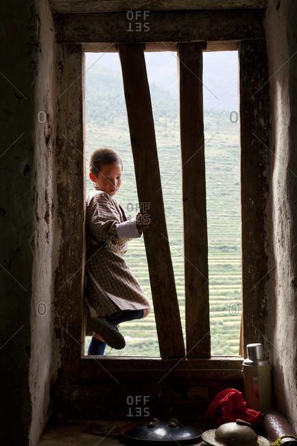 - October 4, 2011: Young Bhutanese boy standing on windowsill at Tshechu Festival at Wangdue Phodrang Dzong, Wangdi, Bhutan