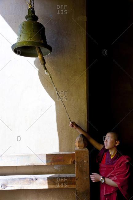 - October 10, 2011: Young monk ringing bell at Tsechu Festival, Gangtey Monastery, Phobjikha Valley, Bhutan