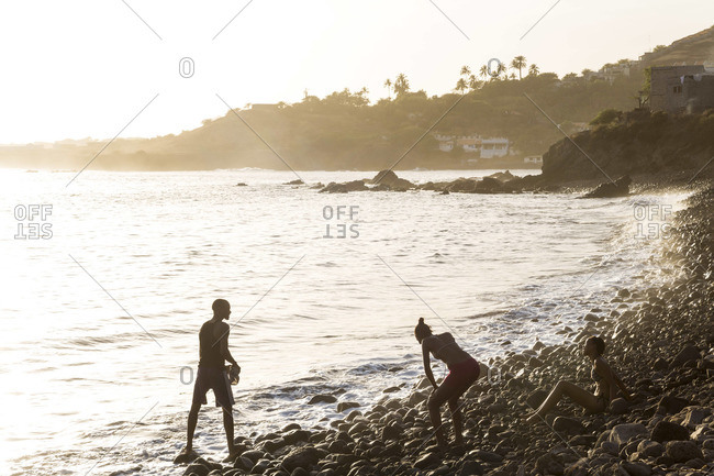 - March 10, 2013: Silhouette of young people on beach, Cidade Velha, Santiago Island, Cape Verde