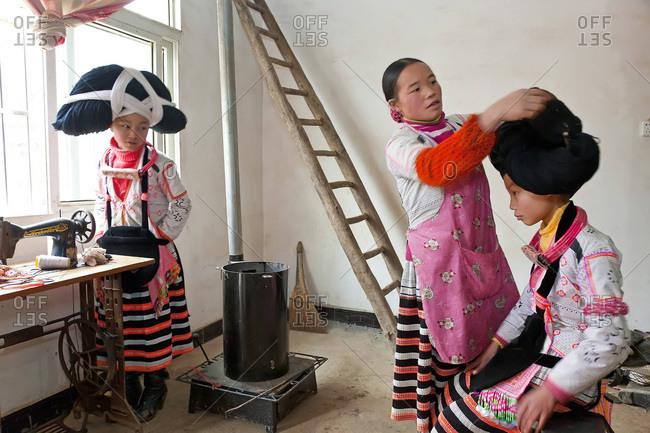 Sugao, Guizhou Province, China - January 30, 2012: Long Horn Miao woman preparing the headdress of a girl, Sugao, Guizhou Province, China