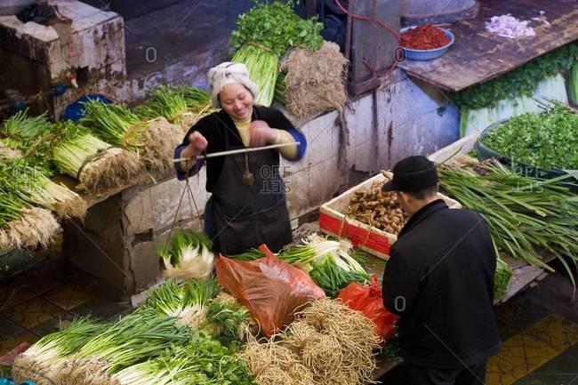 Kaili, Eastern Guizhou, China - March 18, 2008: Women selling vegetables at a market in Kaili, Eastern Guizhou, China