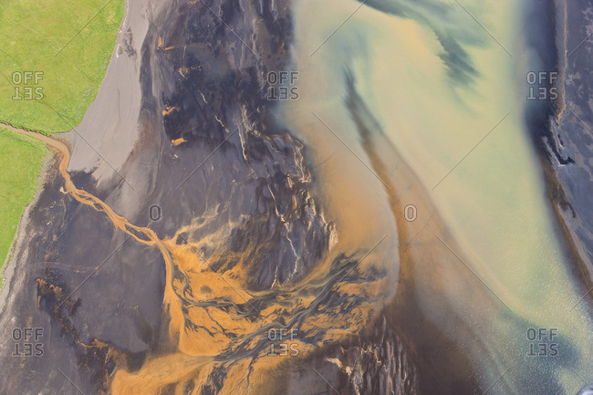 Aerial view of a river estuary colored by sewage outlet, near Hvammur, Iceland