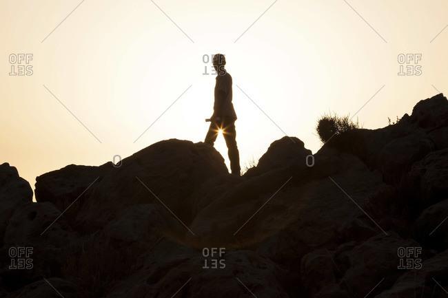 Man on rocks at sunset, Atlas Mountains, Morocco