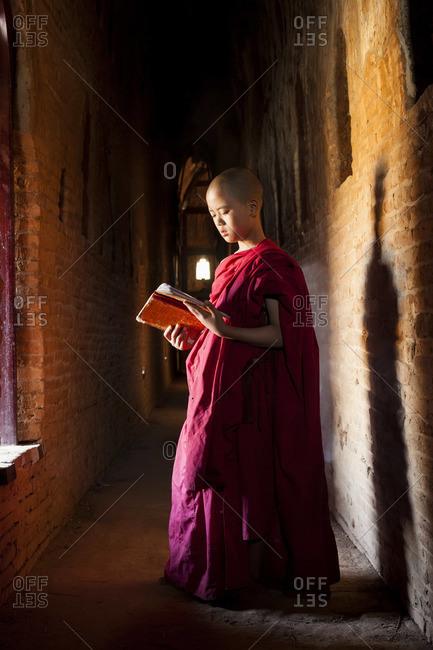 - February 5, 2013: Young monk reading in pagoda, Bagan (Pagan), Myanmar (Burma)