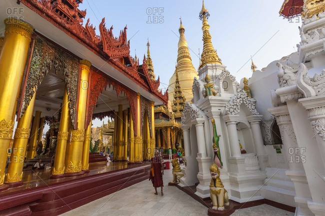 Monk walks by the great golden stupa, Shwedagon Paya (Shwe Dagon Pagoda), Yangon (Rangoon), Myanmar (Burma)