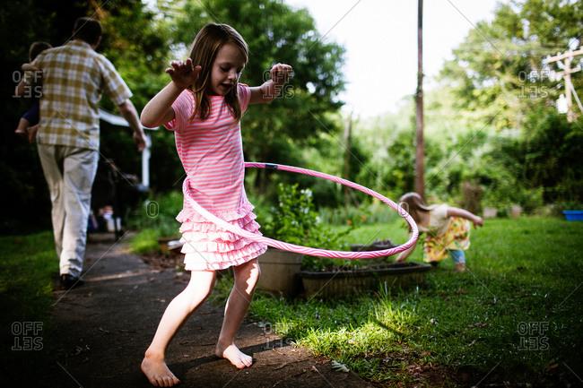 Girl twirling hula hoop in the garden