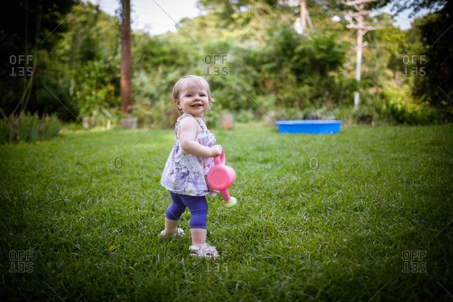 Little girl walking in garden with watering pot