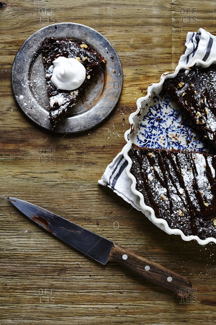 A slice of brownie ganache tart topped with a dollop of coconut creme