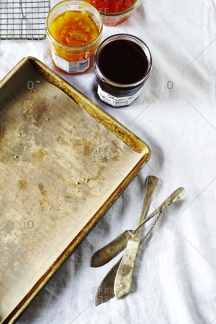 Baking sheet lined in parchment paper, jam and knives
