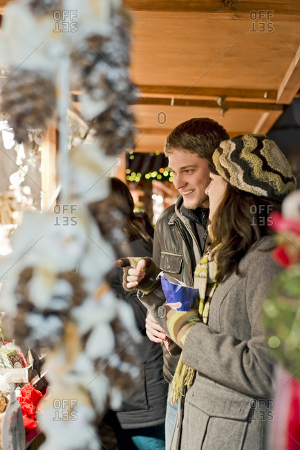Young couple watching offerings at Christmas market