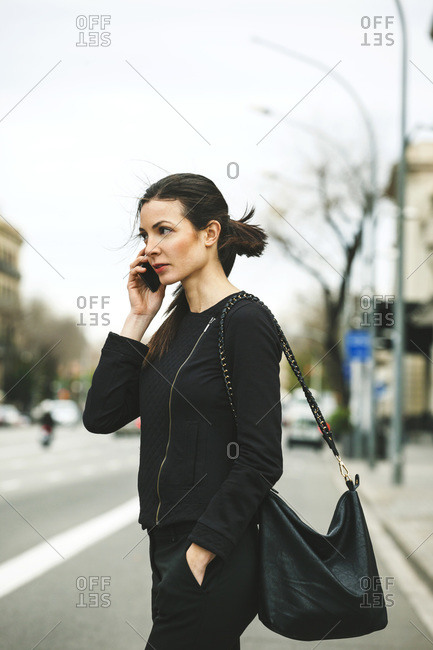 Young black dressed businesswoman telephoning in front of a street