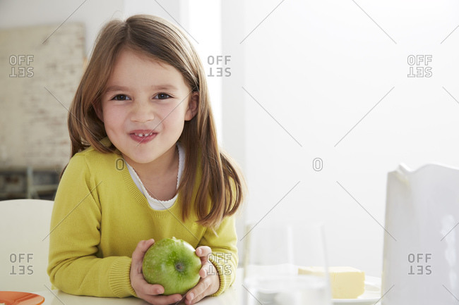 Girl sitting at table with green apple