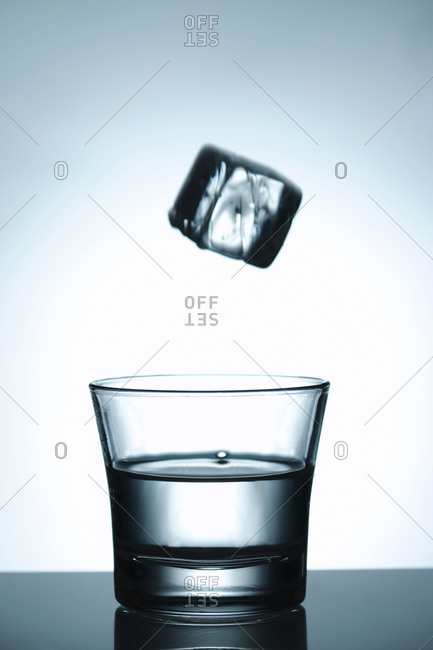 Water glass with flying icecube above the glass, motion blur on the cube