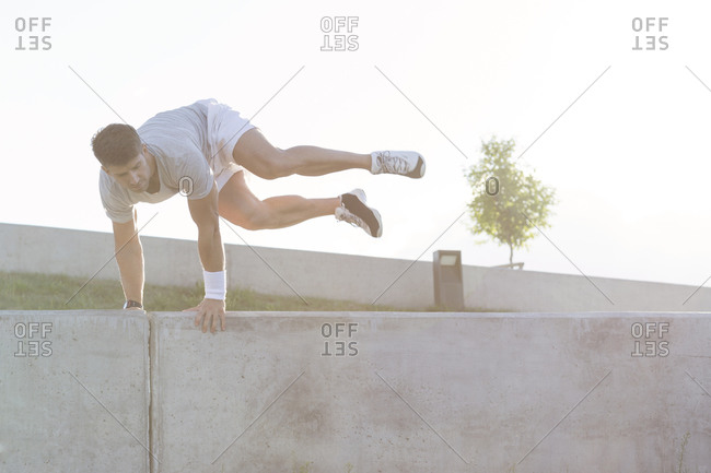 Young man jumping over wall