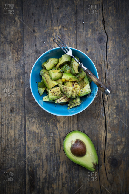 Bowl of avocado salad (Persea americana) and half of avocado on wooden table