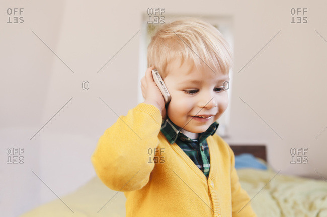 Portrait of smiling toddler telephoning with smartphone