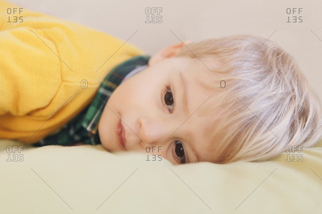 Portrait of toddler laying on bed, close-up