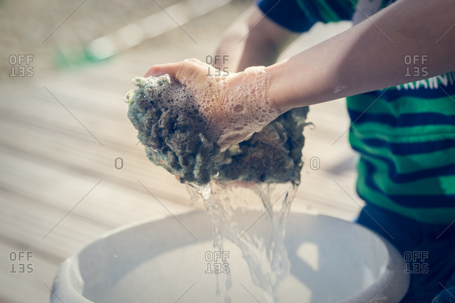 Hands of little boy wringing out cleaning cloth