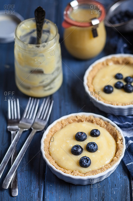 Lemon tartes decorated with blueberries, spoons, empty and full glass of lemon curd on blue wooden table