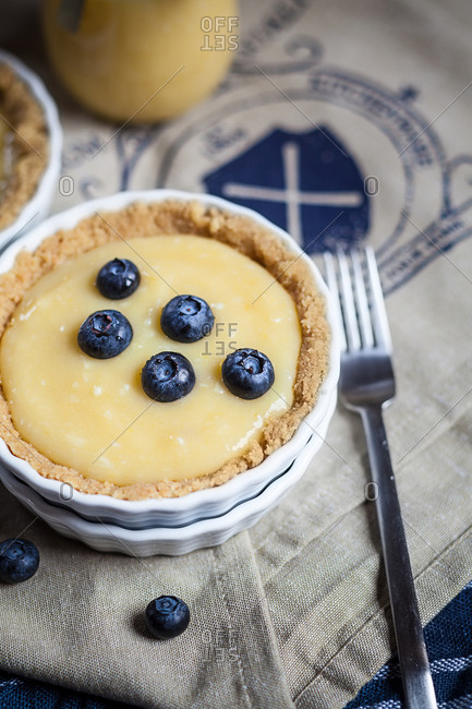 Lemon tart decorated with blueberries and glass and a fork