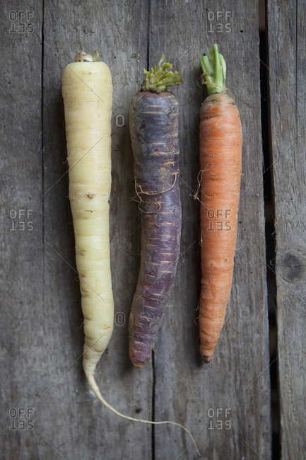 Three types of carrots on wooden surface