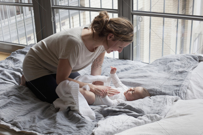 Mother playing with her daughter on the bed