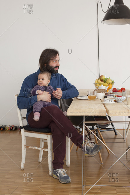 Father and his little daughter sitting by dining table