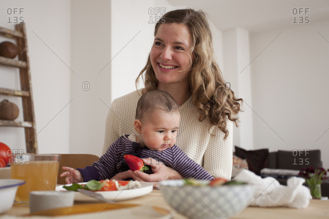 Mother and her little daughter sitting by dining table
