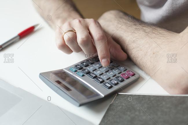 Close up of man using calculator
