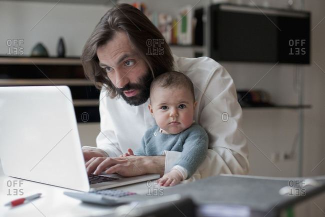 Father working on laptop while his baby sitting on his lap