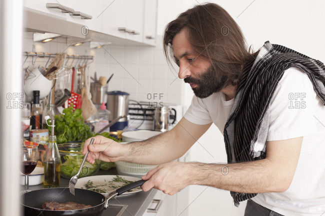 Side view of man making a steak