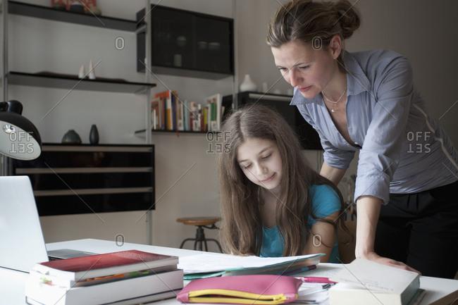 Mother checking teenage girl's homework