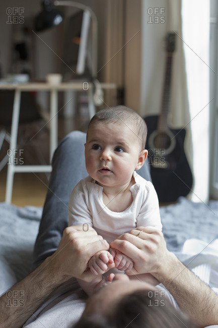 baby girl sitting on his father in living room