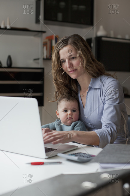 Mother working on laptop while her baby sitting on her lap