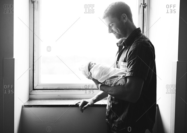 Dad looks at newborn baby in window