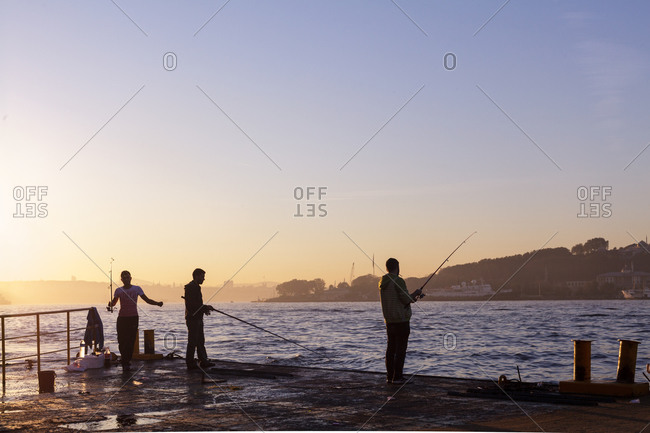 People fish in the early morning on the shore of the Bosforus strait, Istanbul, Turkey