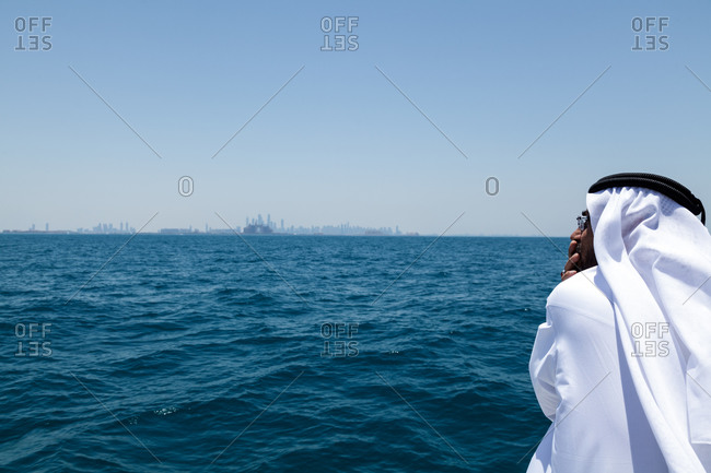 Dubai, UAE  - May 2013: An arab man wearing traditional emirate clothes looks over the Persian Gulf