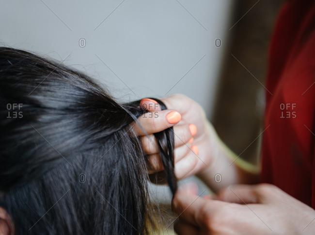 Mom braiding daughter's hair