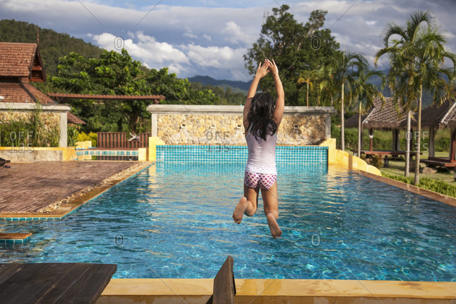 Girl jumping into a swimming pool in Thailand