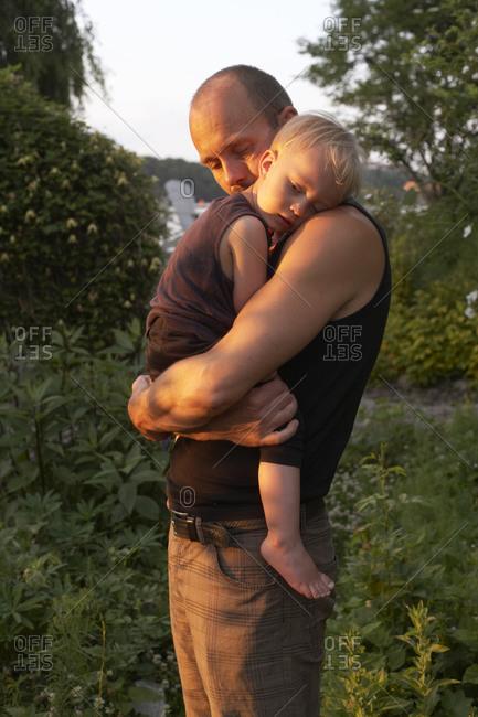 Yong man hugging his daughter in a garden