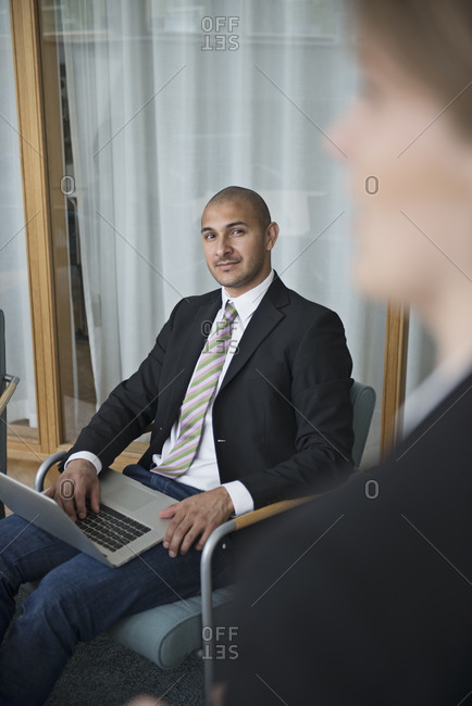 Mid adult man in conference room with laptop, Stockholm, Sweden