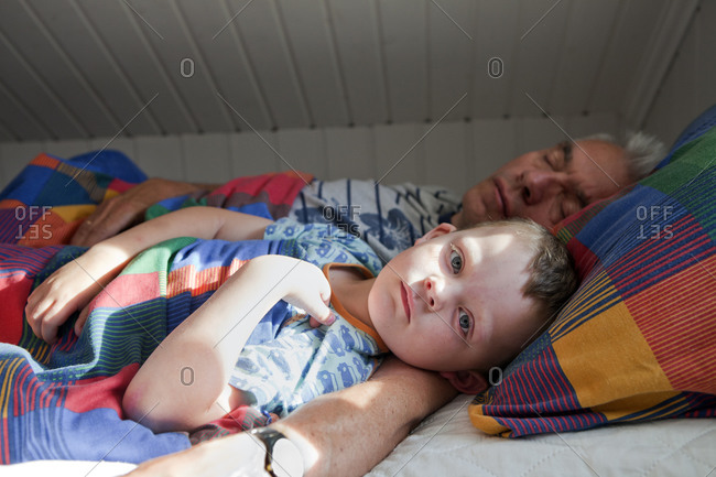 Boy sleeping with his grandfather