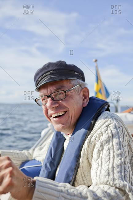 Senior man sailing, Grundsund, Bohuslan, Sweden