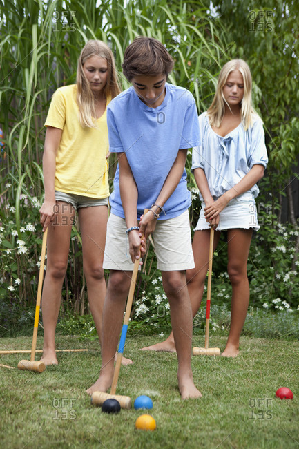 Teenager playing croquet